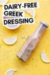 "overhead shot of a bottle of oil-free greek dressing and some of the dressing in a ramekin off to the side surrounded by herbs and lemon slices and a text overlay that reads ""dairy-free greek dressing"""
