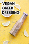 "overhead shot of a bottle of oil-free greek dressing and some of the dressing in a ramekin off to the side surrounded by herbs and lemon slices and a text overlay that reads ""vegan greek dressing"""