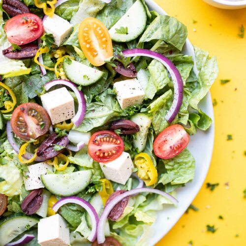 vegan greek salad with a fork and a side of oil-free greek salad dressing