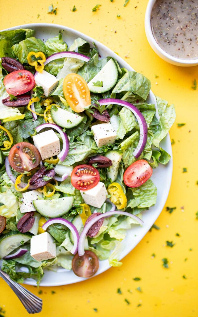 vegan greek salad with a fork and a side of oil-free greek salad dressing