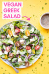 """vegan greek salad with a fork and a side of oil-free greek salad dressing and a text overlay that reads """"vegan greek salad"""""""
