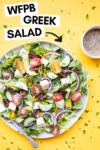 """vegan greek salad with a fork and a side of oil-free greek salad dressing and a text overlay that reads """"wfpb greek salad"""""""