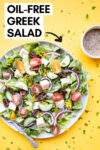 """vegan greek salad with a fork and a side of oil-free greek salad dressing and a text overlay that reads """"oil-free greek salad"""""""