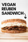 a vegan reuben sandwich on a cutting board and a text overlay that reads vegan reuben sandwich