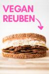 """a vegan reuben sandwich on a cutting board and a text overlay that reads """"vegan reuben"""""""