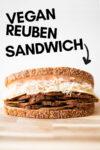 a vegan reuben sandwich on a cutting board and a text overlay that reads vegan reuben sandwich