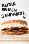 "a vegan reuben sandwich on a cutting board and a text overlay that reads ""seitan reuben sandwich"""
