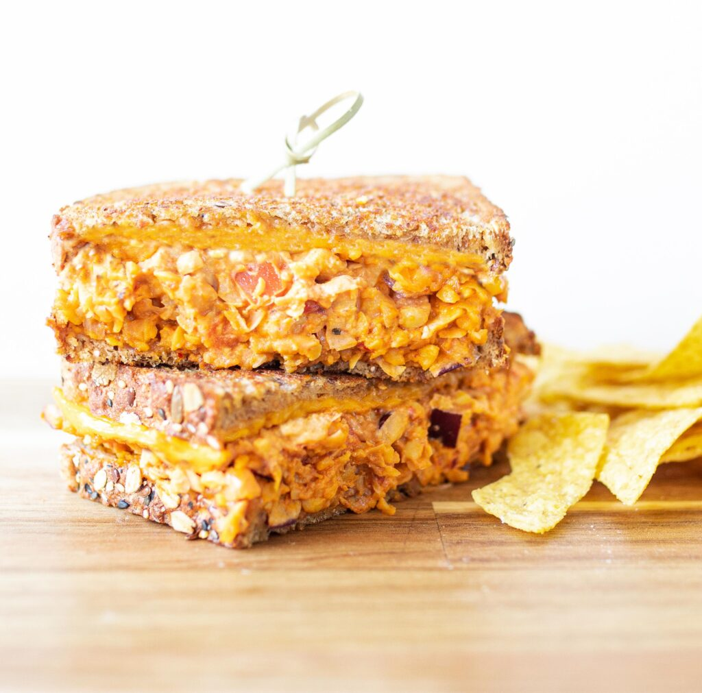 two halves of chipotle chickpea melts stacked on top of each other with a side of tortilla chips