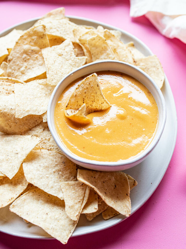 small bowl of vegan nacho cheese surrounded by tortilla chips