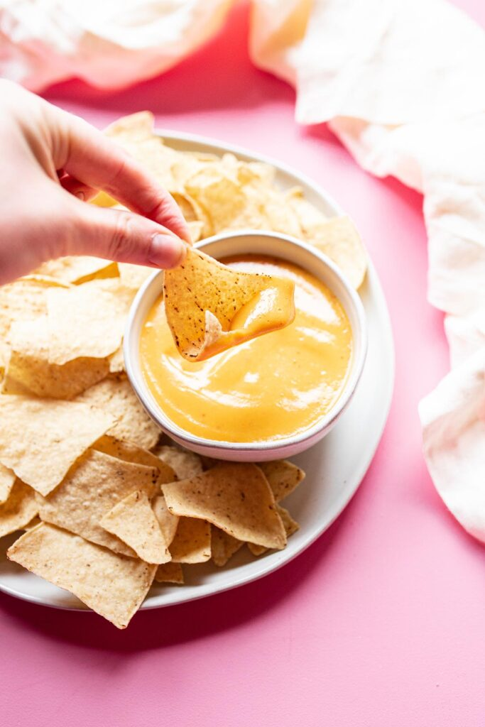 small bowl of vegan nacho cheese surrounded by tortilla chips with a hand holding a dipped chip
