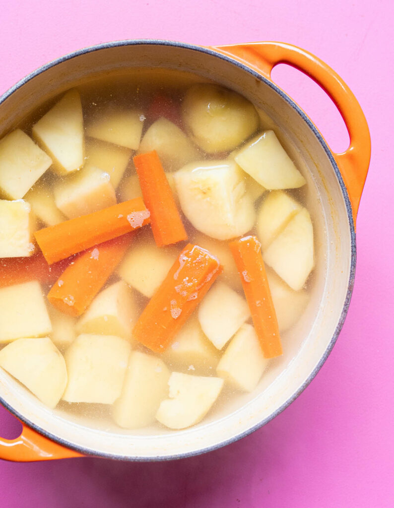 potatoes and carrots in pot with water