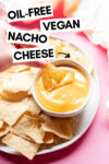 small bowl of vegan nacho cheese surrounded by tortilla chips with a hand holding a dipped chip and a text overlay that reads oil-free vegan nacho cheese