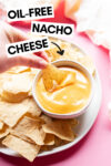 small bowl of vegan nacho cheese surrounded by tortilla chips with a hand holding a dipped chip and a text overlay that reads oil-free nacho cheese