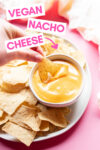small bowl of vegan nacho cheese surrounded by tortilla chips with a hand holding a dipped chip and a text overlay that reads vegan nacho cheese