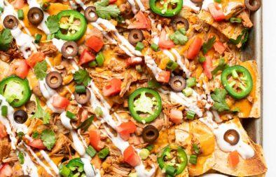 large sheet pan of vegan nachos with a side of salsa
