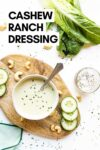 """cucumber cashew ranch dressing in a bowl with a spoon surrounded by cashews, cucumber slices, romaine lettuce, and more with a text overlay that reads """"cashew ranch dressing"""""""