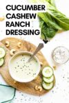 """cucumber cashew ranch dressing in a bowl with a spoon surrounded by cashews, cucumber slices, romaine lettuce, and more with a text overlay that reads """"cucumber cashew ranch dressing"""""""