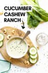 """cucumber cashew ranch dressing in a bowl with a spoon surrounded by cashews, cucumber slices, romaine lettuce, and more with a text overlay that reads """"cucumber cashew ranch"""""""