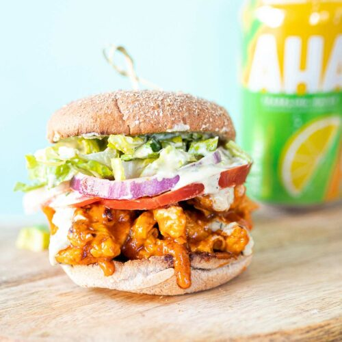 a vegan buffalo chicken sandwich on a wooden slab with a seltzer in the background