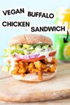 """a vegan buffalo chicken sandwich on a wooden slab with a seltzer in the background and a text overlay that reads """"vegan buffalo chicken sandwich"""""""