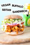 """a vegan buffalo chicken sandwich on a wooden slab with a seltzer in the background and a text overlay that reads """"vegan buffalo seitan sandwich"""""""