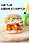 """a vegan buffalo chicken sandwich on a wooden slab with a seltzer in the background and a text overlay that reads """"buffalo seitan sandwich"""""""