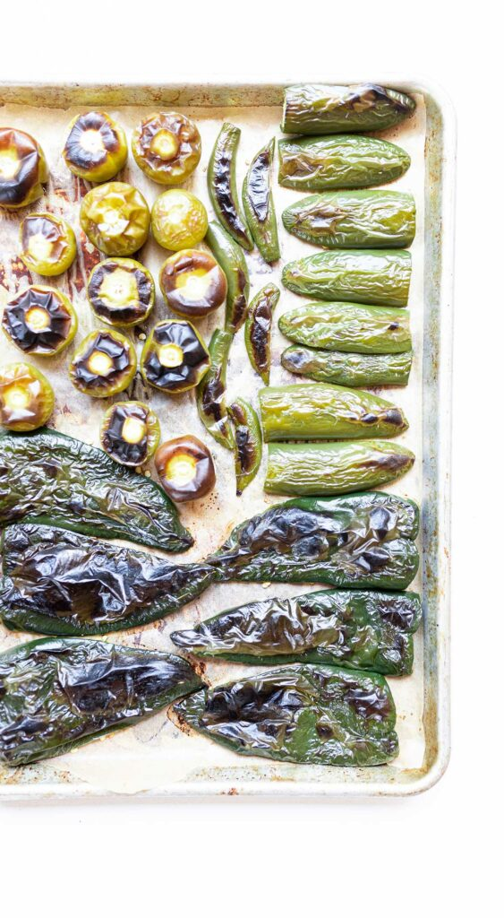 roasted tomatillos, poblano peppers, and serrano peppers on a baking sheet